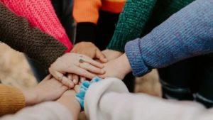 Aufeinandergelegte Hände im Kreis